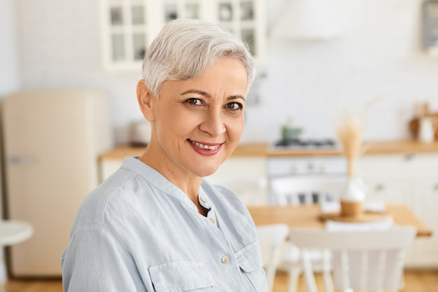Portrait of attractive stylish senior caucasian female pensioner with pixie short hairstyle spending day at home, standing in living room wearing elegant blue dress, smiling happily