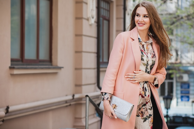 Portrait of attractive stylish smiling woman walking city street in pink coat and floral dress