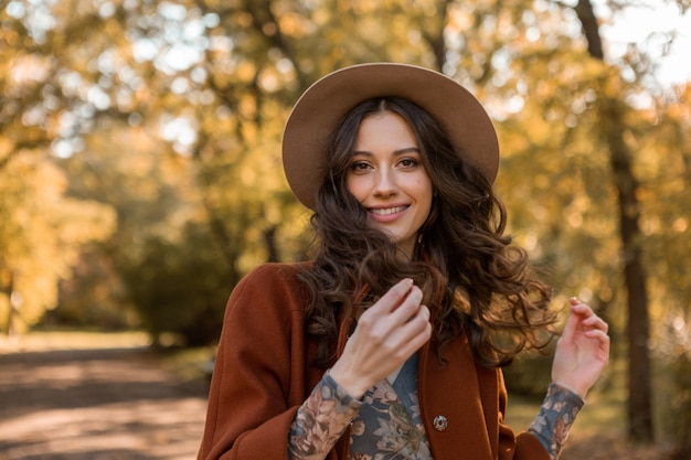 Portrait of attractive stylish smiling woman with long curly hair walking in park dressed in warm brown coat autumn trendy fashion, street style wearing hat