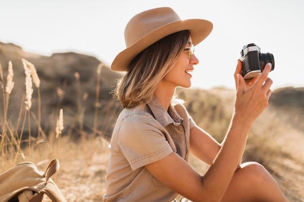 Ritratto di attraente ed elegante giovane donna in abito color cachi nel deserto, viaggiando in africa in safari, indossando un cappello, prendendo foto sulla fotocamera vintage