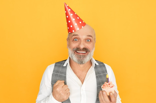 Portrait of attractive successful senior bearded businessman wearing cone hat expressing excitement, enjoying birthday party, holding cupcake with one candle