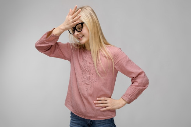 Portrait of attractive sweet smiling adorable blonde teenager girl in glasses in pink blouse o