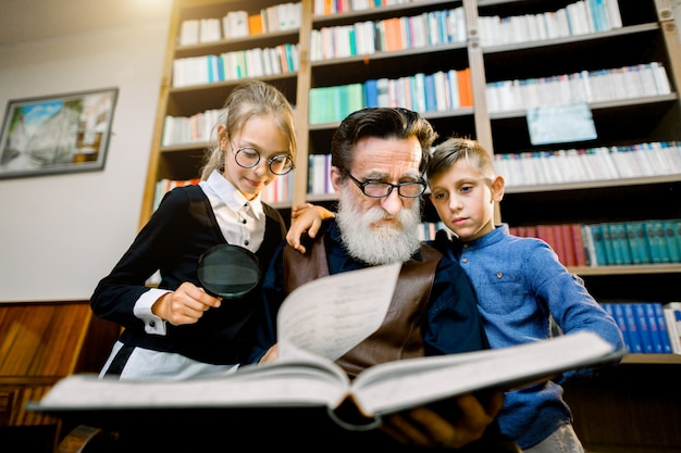 Portrait of attractive teen grandchildren and experienced senior bearded grandfather which spending time together in the library on reading interesting book. bookcase on the background