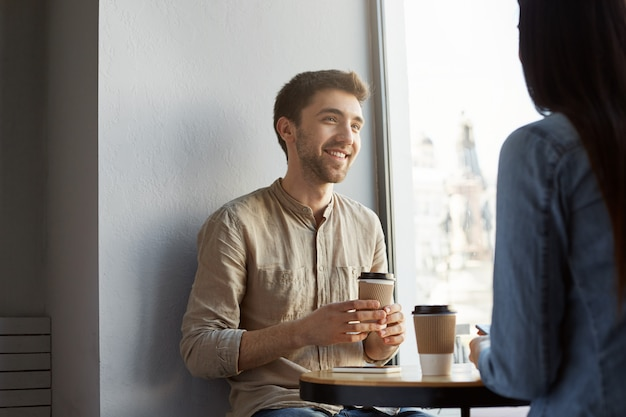 Portrait of attractive unshaved young guy with dark hair, smiling, drinking coffee and listening to girlfriend stories about hard day at work. lifestyle, relationship concept