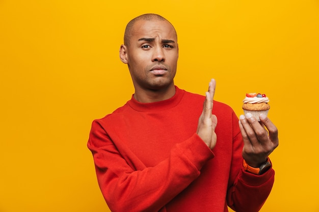 Portrait of an attractive upset casual young african man standing over yellow wall, refusing to eat cupcake