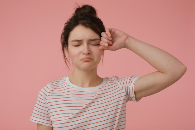 Portrait of attractive, upset girl with brunette hair and bun. wearing t-shirt with red strips and rub an eye. emotional concept. stand isolated over pastel pink wall