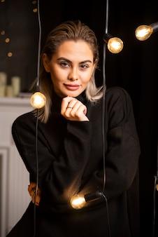 Ritratto di donna attraente in maglione nero in piedi e in posa