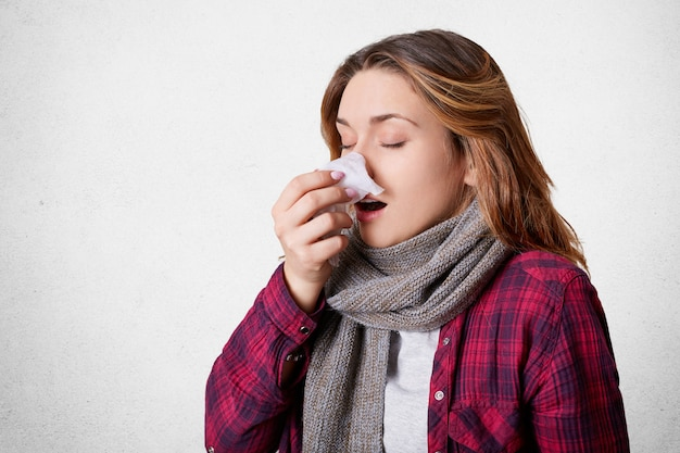 Portrait of attractive woman caught cold, blows nose in tissue, suffers from cold, has running nose, being upset as spends time indoor