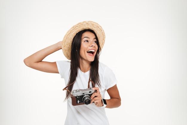 Ritratto di una donna attraente con cappello in possesso di una macchina fotografica