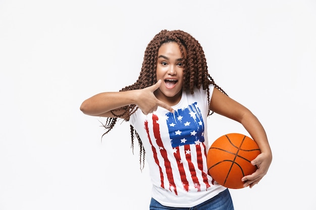 Portrait of attractive woman holding basketball during game while standing isolated against white wall