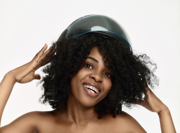 Ritratto di donna attraente in casco da moto sulla parete bianca dello studio