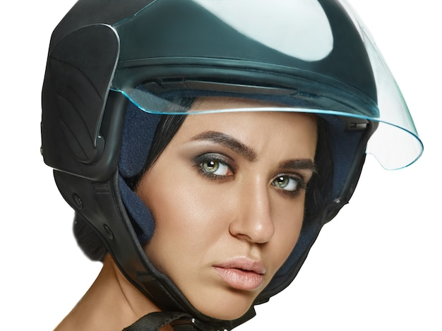 Portrait of attractive woman in motorbike helmet on white  wall. beauty and skin protection concept