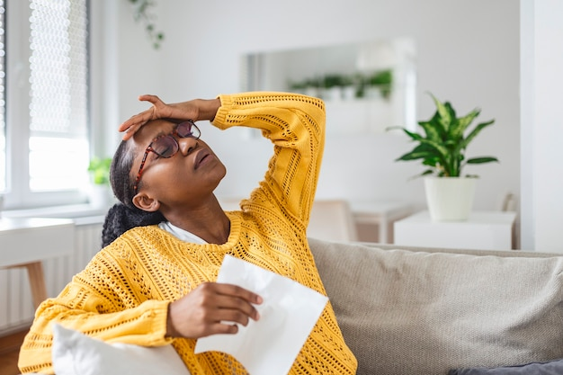 Portrait of an attractive woman sitting on a sofa at home with a headache, feeling pain and with an expression of being unwell. upset depressed woman lying on couch feeling strong headache migraine.