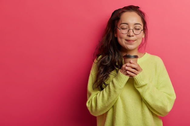 Portrait of attractive woman smells aromatic coffee, has break, closes eyes with pleasure, wears transparent glasses and oversized jumper