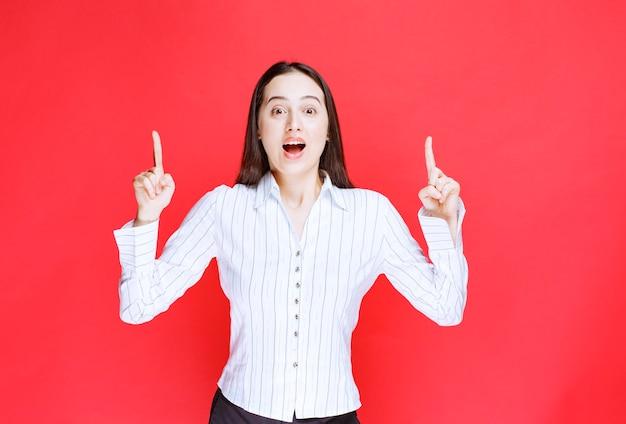 Ritratto di donna attraente in piedi e puntare le dita contro il muro rosso.