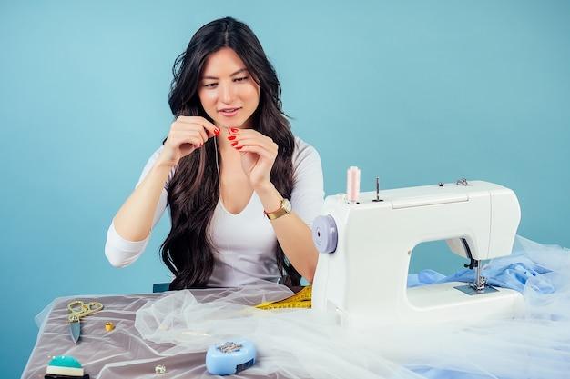 肖像画の魅力的な女性の仕立て屋(仕立て屋)は、スタジオの青い背景のミシンに針を通します。新しい服のコレクションを作成するというコンセプト