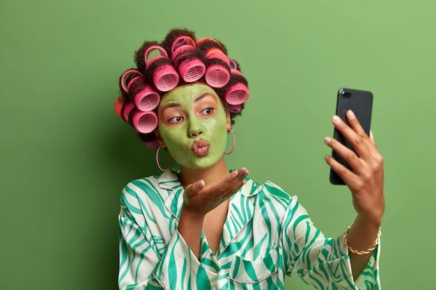Ritratto di donna attraente prende selfie, manda un bacio d'aria di smart phone, ha umore romantico, fa foto per il marito, applica una maschera nutriente verde sul viso,