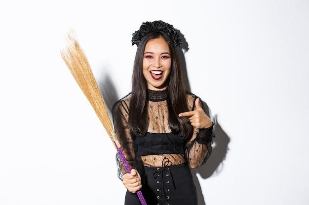 Ritratto di donna attraente in costume da strega che celebra halloween, indicando la scopa, in piedi su sfondo bianco.