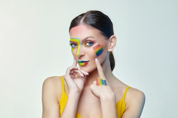 Portrait of an attractive woman with bright makeup with rainbow lgtb flag