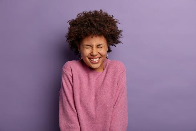 Ritratto di donna attraente con acconciatura riccia, scherza felicemente, sente una storia divertente e divertente, indossa un maglione casual