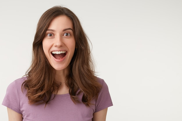 Portrait of attractive woman with long dark hair, expressing surprise and shock