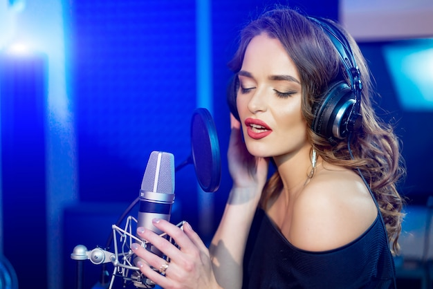 Portrait of attractive woman with perfect makeup recording a song in a professional studio.