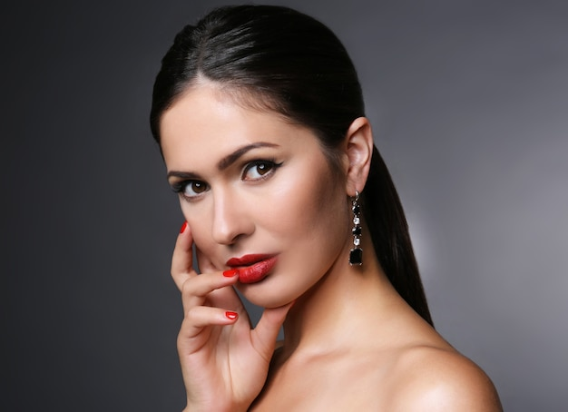 Portrait of attractive woman with red lips on grey background