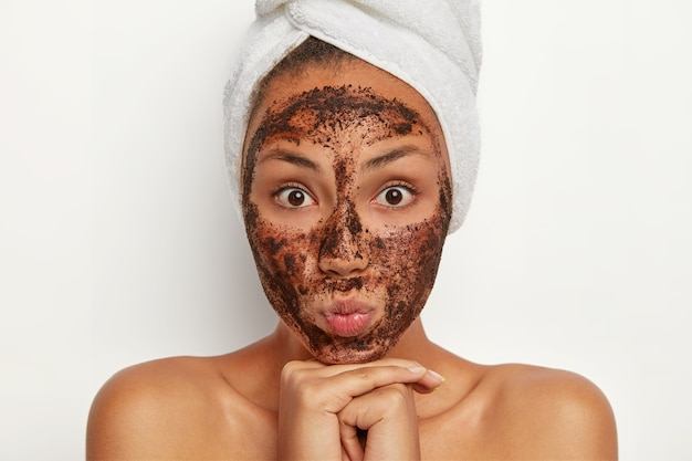 Portrait of attractive woman with surpised expression, has coffee scrub around face, cleanses from pores, removes dead cells, chooses mask to suit her skin, stands topless after shower, towel on head