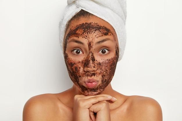 Ritratto di donna attraente con espressione sorpresa, ha uno scrub al caffè intorno al viso, purifica dai pori, rimuove le cellule morte, sceglie la maschera per adattarsi alla sua pelle, sta in topless dopo la doccia, asciugamano sulla testa