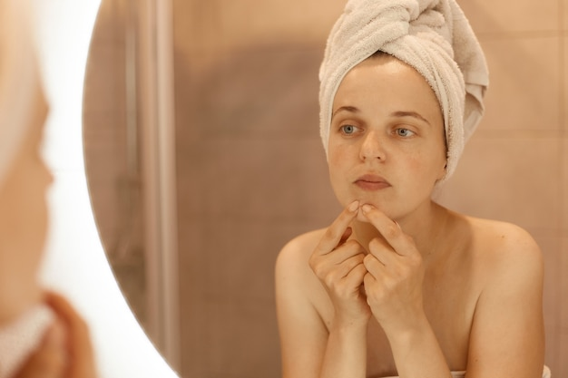 Portrait of attractive woman wrapped in white towel standing with bare shoulders in bathroom and looking for or squeezing acne on chin, having sad expression.