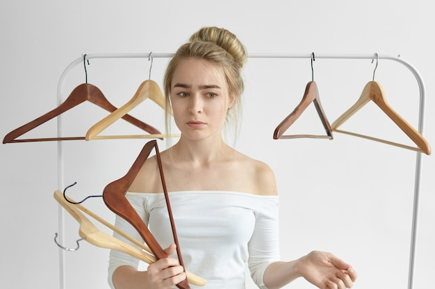Portrait of attractive worried woman with hair bun posing against white wall, holding racks in her hands while cleaning her wardrobe, getting rid off useless clothes. nothing to wear