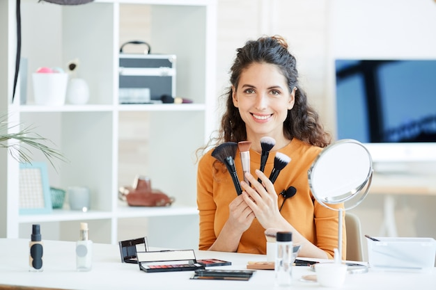 Portrait of attractive young adult woman sitting at table holding various make-up brushes
