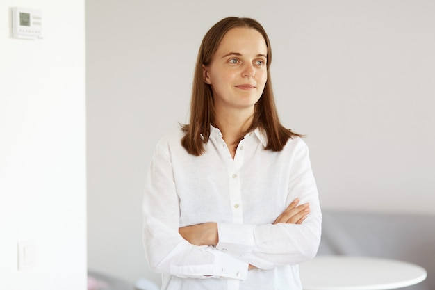 Portrait of attractive young adult woman with dark hair wearing white casual style shirt, standing with folded arms, looking away with confident expression.