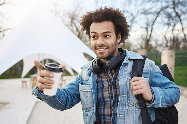 Portrait of attractive young african-american with afro hairstyle holding backpack and coffee, wearing trendy clothes and headphones over neck, pointing somewhere