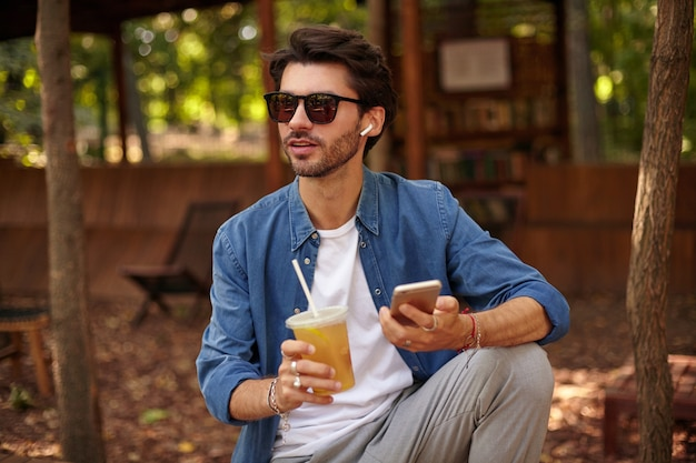 Portrait of attractive young bearded man with cup of ice tea in hand, looking away and holding smartphone, wearing earphones and sunglasses