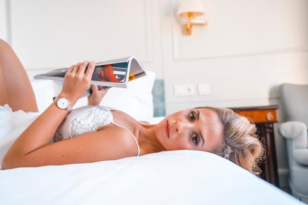 잡지를 읽고 호텔 침대에서 잠옷에 세로 매력적인 젊은 금발 백인 여자