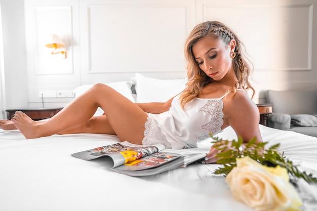 꽃과 함께 잡지를 읽고 호텔 침대에 잠옷에 세로 매력적인 젊은 금발 백인 여자