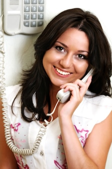 Portrait of attractive young brunette woman smiles and holds of phone handset near head. happy girl talking with friend at home
