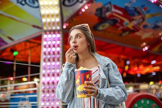 Ritratto di attraente giovane donna bruna con occhiali da sole sulla sua testa che mangia popcorn mentre si cammina nel parco di divertimenti, guardando da parte con interesse