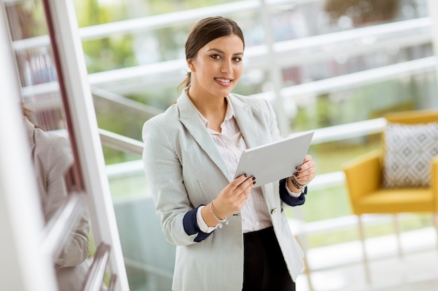 Portrait of attractive young business woman smiling confidently and working online with a digital tablet while standing in a modern office