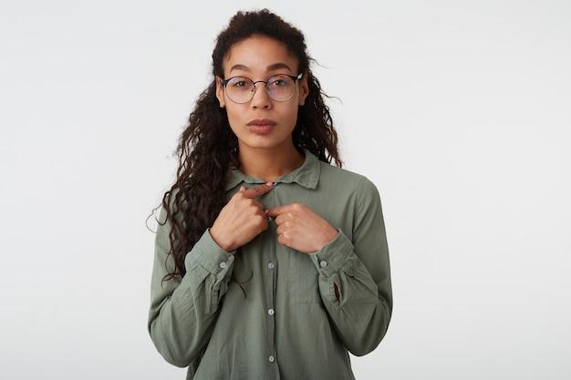 Ritratto di attraente giovane signora dai capelli scuri ricci con la pelle scura che guarda l'obbiettivo con le labbra piegate mentre allaccia i pulsanti sulla sua camicia, isolato su sfondo bianco