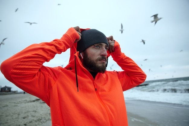 Portrait of attractive young dark haired man with beard dressed in warm sporty clothes putting on hood while posing over beach on grey overcast weather, looking thoughtfully ahead