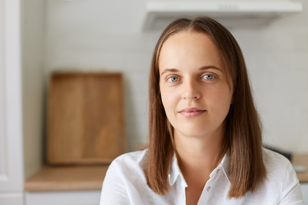 Portrait of attractive young dark haired woman at home in light room, beautiful female looking at camera with calm facial expression, wearing white shirt, indoor shot.