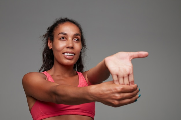 Portrait of attractive young dark skinned curly brunette woman dressed in athletic pink top while standing, looking positively ahead while stretching her arm