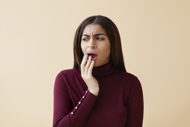 Portrait of attractive young dark skinned female having bored facial expression, looking away, covering mouth while yawning, feeling tired during working day at office. human gestures and signs