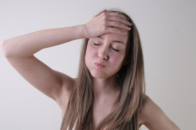 Ritratto di una giovane donna attraente con un viso infastidito in piedi contro un muro bianco