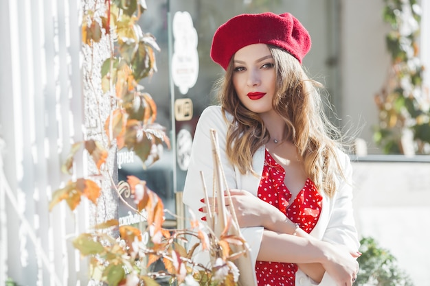 Portrait of attractive young girl outdoors. beautiful urban lady looking at camera. female with red lips.