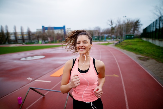 Portrait of attractive young happy fitness girl jogging while listening to music outside on running track.