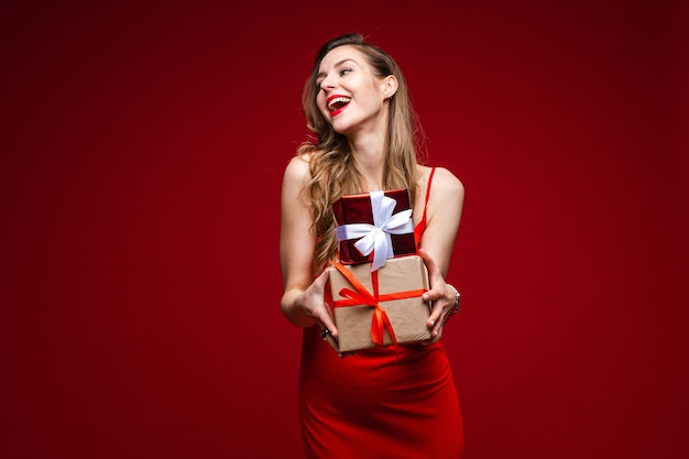 Portrait of attractive young lady in red silk dress holding small wrapped presents