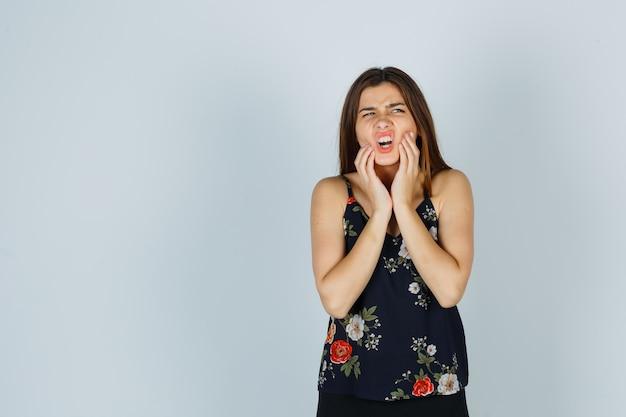 Ritratto di una giovane donna attraente che soffre di mal di denti in camicetta e che sembra una vista frontale dolorosa